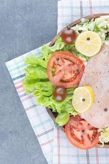 Filetti di pollo e verdure a fette sul piatto di legno.