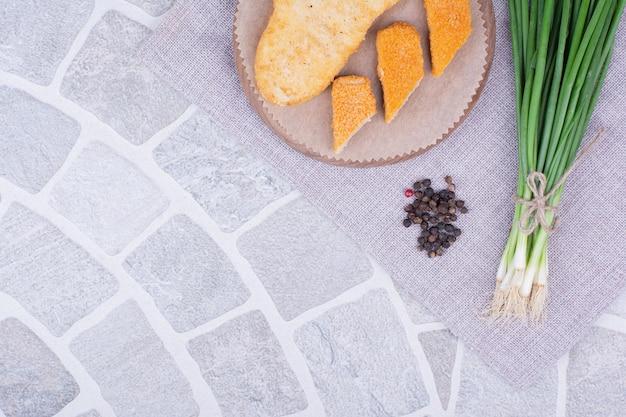 Pepite di pollo e pesce su una tavola di legno con cipolle verdi