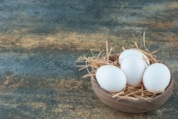 Chicken fresh white eggs lying in hay on wooden bowl
