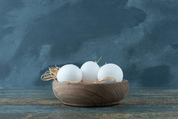 Pollo uova bianche fresche che si trovano nel fieno sulla ciotola di legno