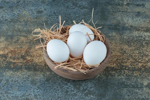 木製のボウルに干し草で横たわっている鶏の新鮮な白い卵