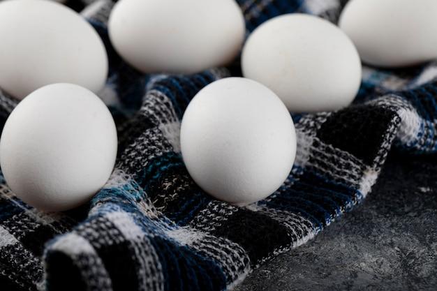 Uova bianche fresche di pollo sulla tovaglia