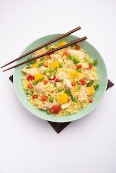 チキンチャーハンは、人気のあるインド風中華またはインドシナの屋台の食べ物で、箸で皿に盛り付けられます