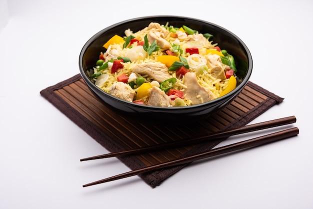 Жареный рис с курицей - популярная индийская китайская или индокитайская уличная еда, которую подают на тарелке с палочками для еды.