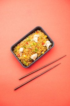 Жареный рис с курицей, упакованный в черный пластиковый контейнер для онлайн-заказа еды. популярный индокитайский рецепт