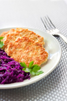 Chicken fritters and stewed red cabbage with caraway seeds