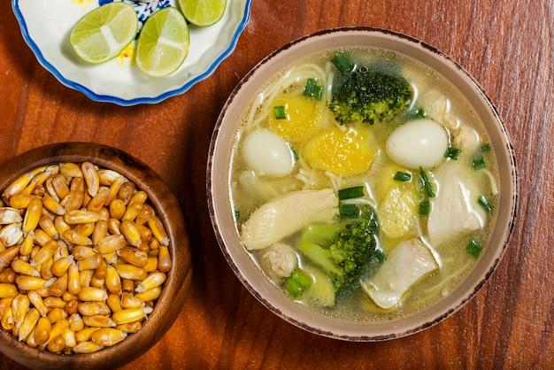 ブロッコリー、ウズラの卵、レモン、トーストしたペルーコーンを添えた高麗人参のスープ。上面図。