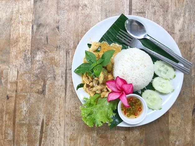 チキングリーンカレー。木製のテーブルの上のプレートのグリーンカレーチキン。タイ料理はdeliciです