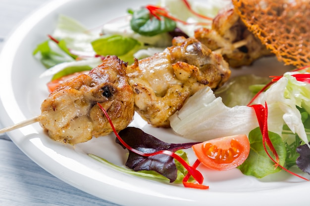 Chicken grilled meat on stick with salad and tomatoes on white plate