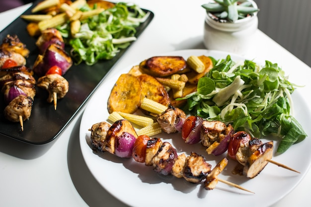 Chicken grilled skewers with lamb salad and baby corn