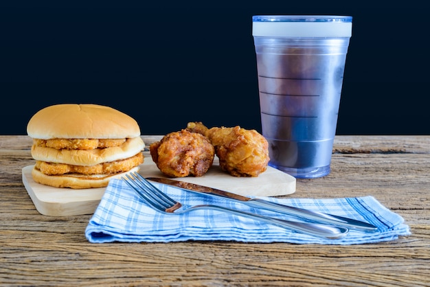 Chicken hamburger and fried chicken, glass of cola on wooden cutting board with knife and fork, napkin