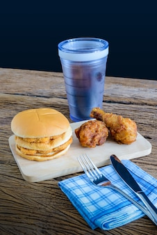 Chicken hamburger and fried chicken, glass of cola on wooden cutting board with knife