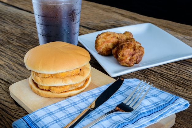 Chicken hamburger and fried chicken, glass of cola on wooden cutting board with knife, for