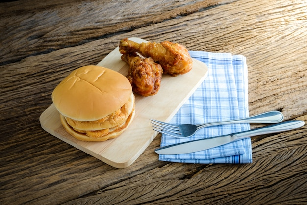 Chicken hamburger and fried chicken on wooden cutting board with knife and fork, napkin