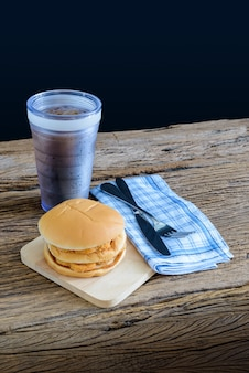 Chicken hamburger and glass of cola on wooden cutting board with knife and fork, napkin