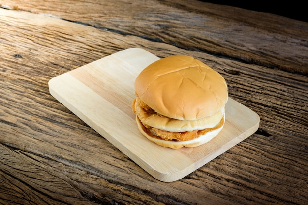 Chicken hamburger on wooden cutting board, on table