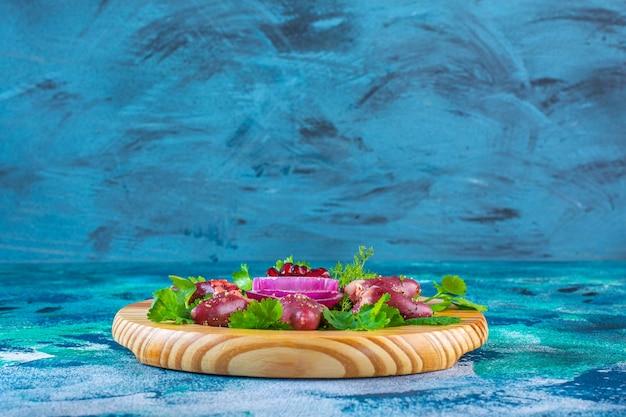 Cuori di pollo e cipolla affettata con arilli di melograno su un piatto di legno
