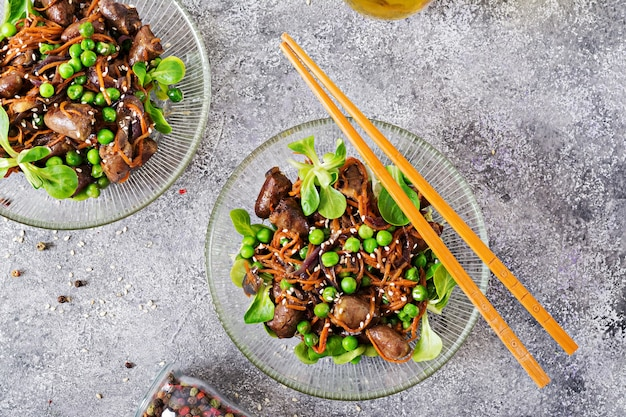 Chicken hearts with carrots, onions and green peas in asian style. top view