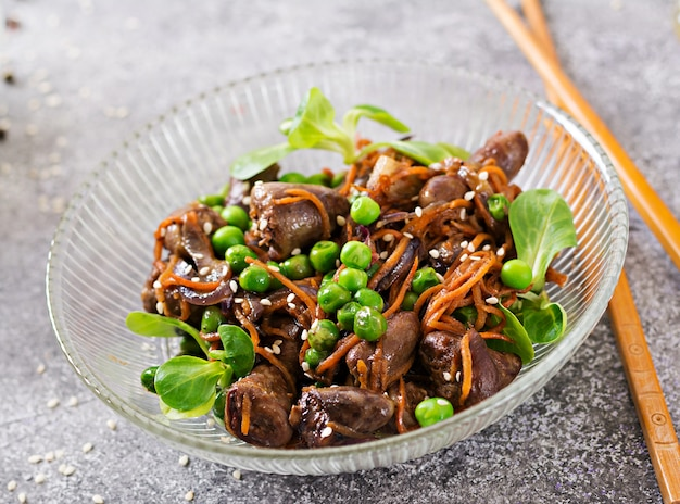 Chicken hearts with carrots, onions and green peas in asian style.
