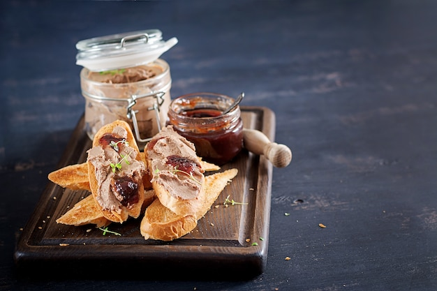 Chicken homemade liver pate in glass jar with toasts and lingonberry jam with chili.