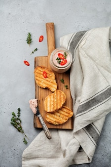 Chicken homemade pate from liver with red pepper, thyme twigs and toasted bread slices on wooden old board on gray concrete or stone.