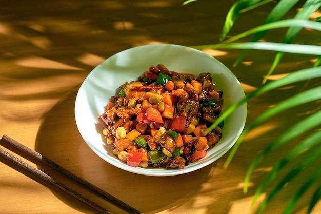 Курица в кисло-сладком соусе, с сычуаньским перцем, арахисом в белой миске. деревянный фон. китайская кухня