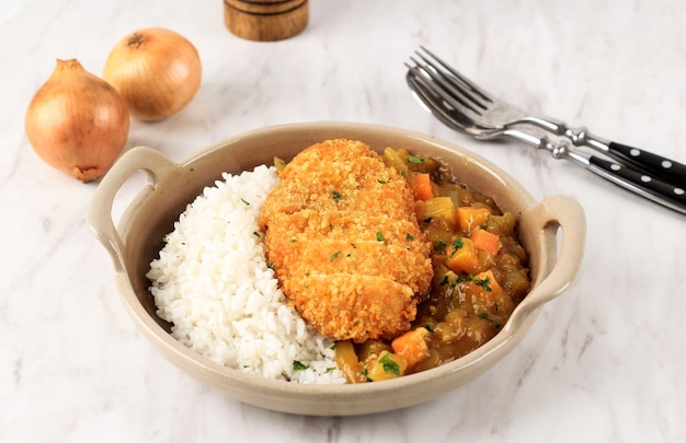일본식 카레를 곁들인 치킨 카츠, 흰색 대리석 테이블 위의 갈색 세라믹 접시에 흰 쌀과 함께 제공, 텍스트 또는 레시피 복사 공간 포함