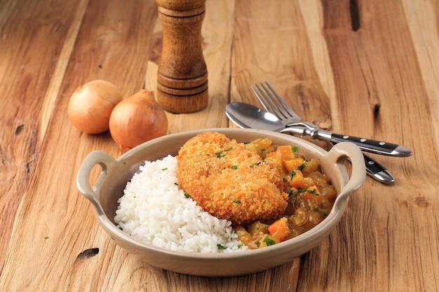 일본 카레를 곁들인 치킨 카츠, 나무 테이블 위의 갈색 세라믹 접시에 흰 쌀과 함께 제공