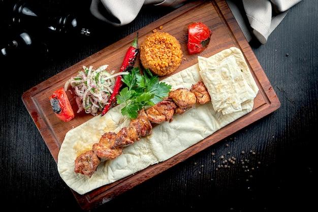 치킨 케밥은 lavash, bulgur 및 나무 보드에 구운 야채와 함께 그릴에서 요리했습니다. 터키 케밥. 닫기, 선택적 초점