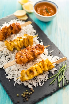 Chicken kebab and rice near condiments