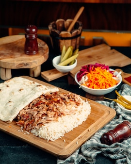 Chicken kebab slices served with rice and flatbread places on serving board