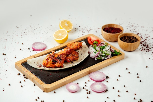Chicken kebab with onions on a wooden board