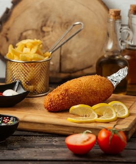 Chicken kiev served with fries, lemon, mayonnaise and ketchup