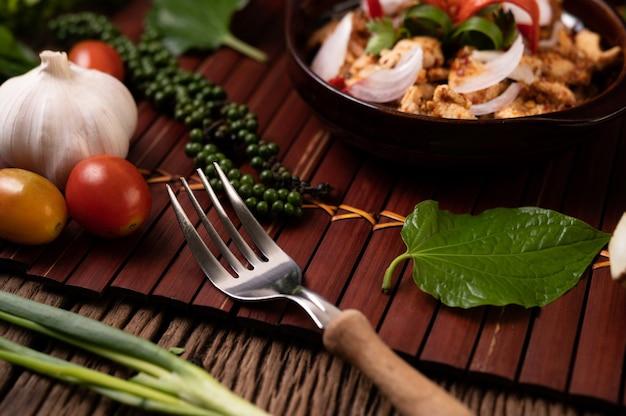 Куриный ларб на тарелке с сушеным перцем чили, помидорами, зеленым луком и салатной вилкой.