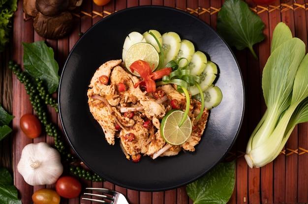 Куриный ларб на тарелке с сушеным перцем чили, помидорами, зеленым луком и листьями салата