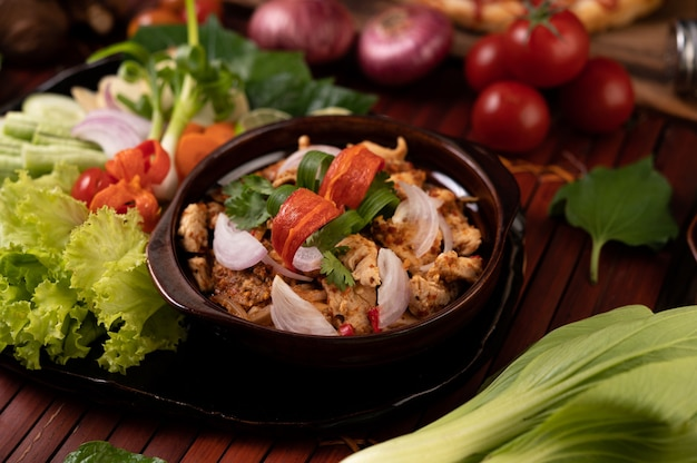 Chicken larb on the plate with dried chilies, tomatoes, spring onions and lettuce