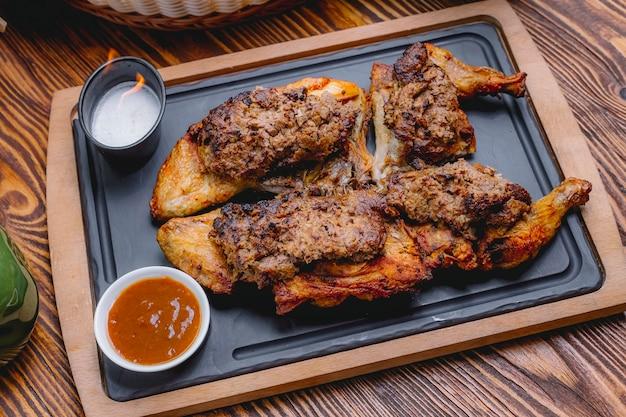 Куриные лаванги на деревянной доске, грецкие орехи, лук, сливы, вид сбоку
