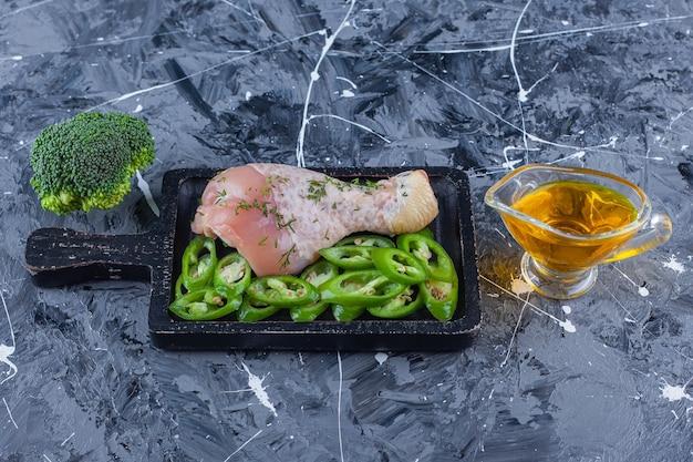 파란색 표면에 기름과 브로콜리 옆에 보드에 닭 다리와 슬라이스 고추