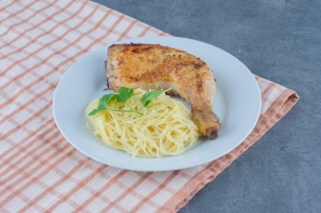 Coscia di pollo e spaghetti sul piatto bianco.