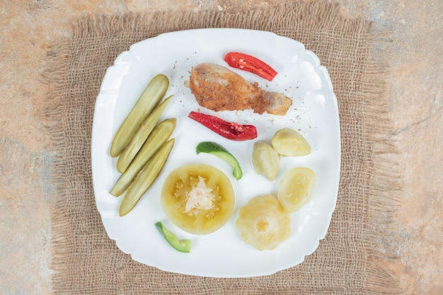 Coscia di pollo con vari sottaceti su piatto bianco