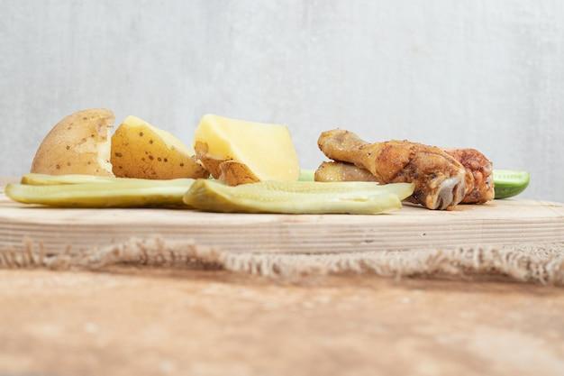 Coscia di pollo con varie verdure su tavola di legno