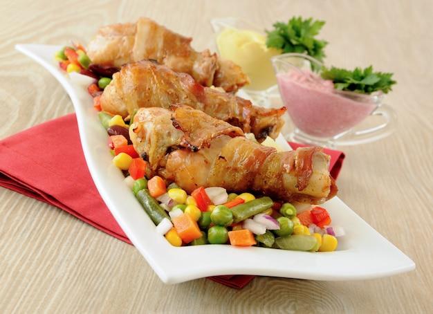 야채와 소스를 곁들인 베이컨으로 감싼 닭 다리