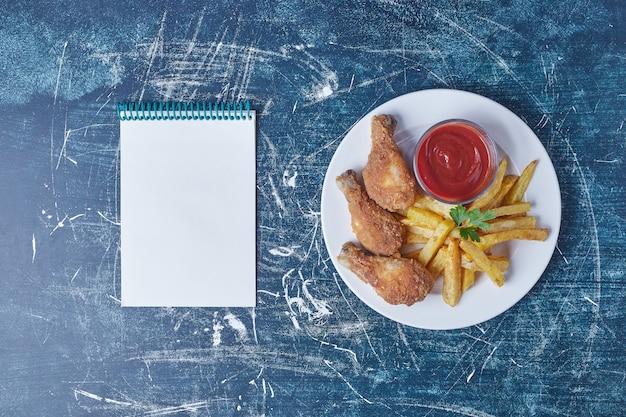노트북과 함께 하얀 접시에 닭 다리와 튀긴 감자.