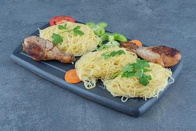 Куриные ножки и спагетти на деревянной доске.