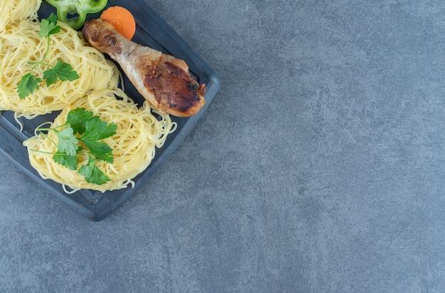 木の板に鶏の脚とスパゲッティ。