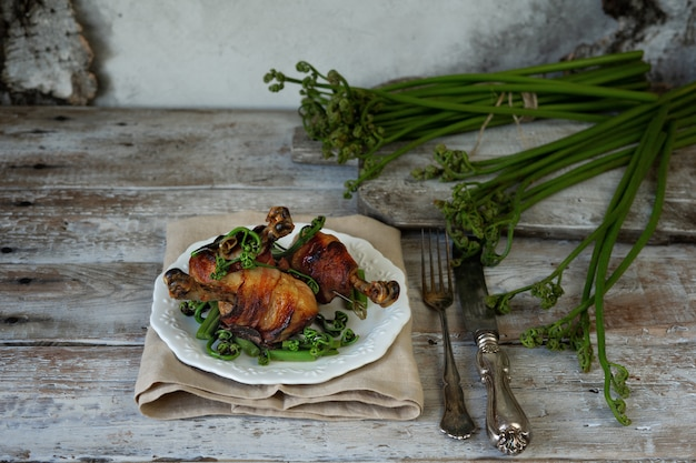 Chicken legs in bacon and fried bracken on a vintage plate.