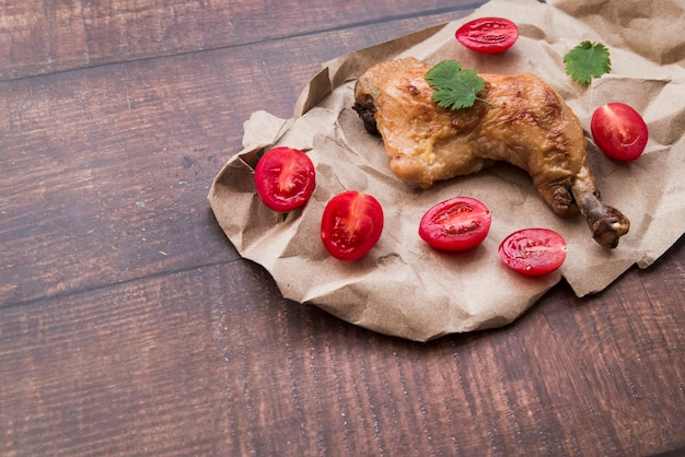 Chicken legs on brown paper with halved tomatoes on wooden table