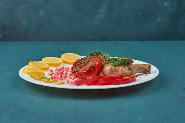Cosce di pollo in un piatto bianco con verdure e spezie.