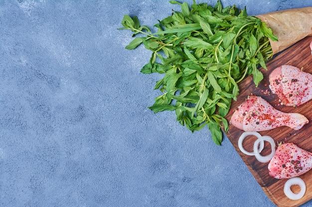 Куриные ножки с зеленью на деревянной доске на синем