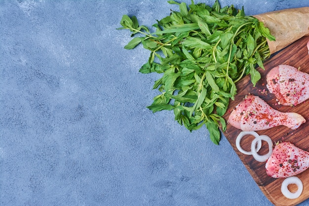Cosce di pollo alle erbe su una tavola di legno sul blu